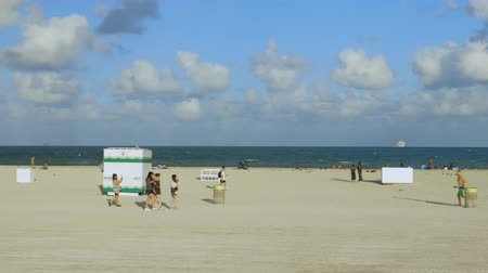 merging : People on Miami Beach relax on sandy beach a beautiful sunny day on the dark blue Atlantic Ocean merging with a blue sky background. Miami USA. 24092019.
