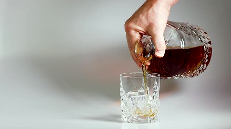 Short film showing whiskey being poured into a tumbler glass with ice on white background. Slow motion. Beautiful backgrounds. Alcohol concept.