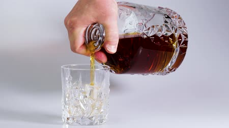 pohárek : Short film showing whiskey being poured into a tumbler glass with ice on white background. Beautiful backgrounds. Alcohol Dostupné videozáznamy
