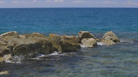 Gorgeous view of waves braking on stones. Turquoise water of Atlantic ocean and big rocks on blue sky background. Willemstad. Curacao. Wideo