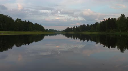 Gorgeous summer evening. Crystal clear mirror water surface. Sky covered with heavy clouds.