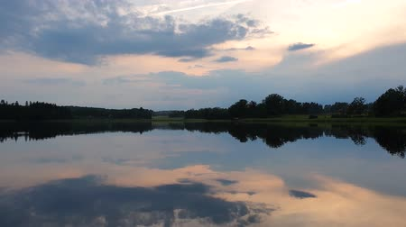 Slow motion. Gorgeous view of sunset on calm summer evening. Lake shore with green trees and plants reflecting in crystal clean mirror water surface. Sky covered with heavy thunder clouds. Wideo
