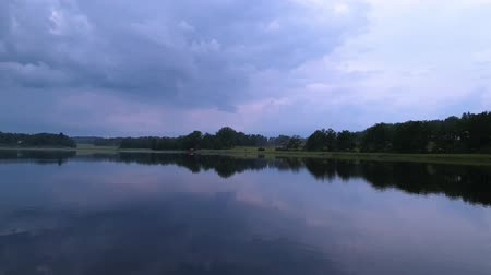 гром : Slow motion. Gorgeous view of sunset on calm summer evening. Lake shore with green trees and plants reflecting in crystal clean mirror water surface. Sky covered with heavy thunder clouds. Стоковые видеозаписи