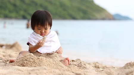 play : Footage of asian baby play sand on the beach Stock Footage