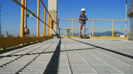 biztonság : Engineer with safety suit to standing on platform of industrial plant