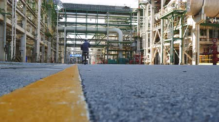 нефтехимический : A man stand alone in process area of petrol and chemical refinery factory in day time