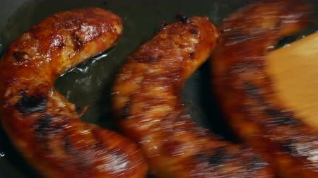 simmer : Overhead Closeup frying link sausage fast food in cast iron skillet Stock Footage