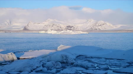 iceberg : Timelapse of the Iceland mountains with sky range seen from the Ice Lake with icebergs in clear day with fog