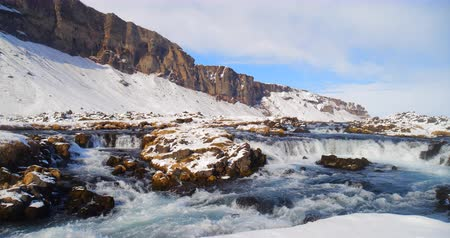 eco tourism : Frozen river with waterfall, winter snowy landscape in mountain. Stock Footage