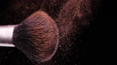 kompakt : Make up brush with colored brown powderon at black background Slow Motion