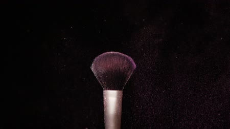 Make up brush with colored purple powderon at black background Slow Motion