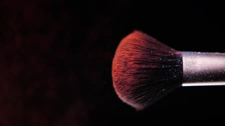 Make up brush with colored red powderon at black background Slow Motion Стоковые видеозаписи
