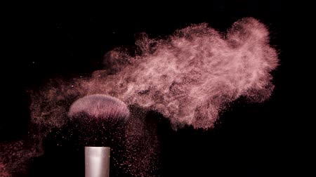 kompakt : Make up brush with colored pink powderon at black background Slow Motion