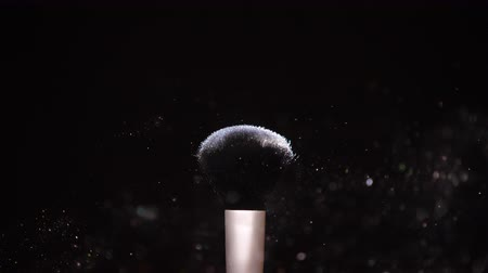 Make up brush with colored white powderon at black background Slow Motion