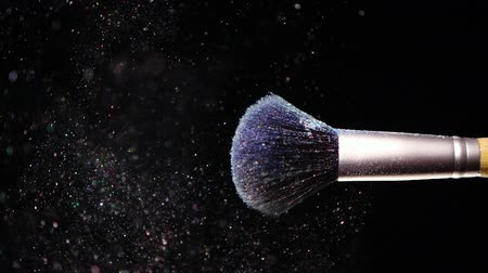 Make up brush with colored blue powderon at black background Slow Motion