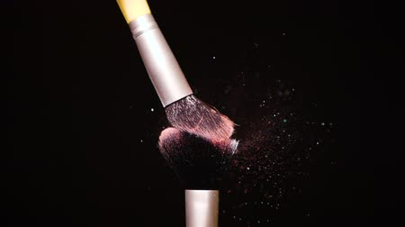 kompakt : Make up brush with colored Pink powder at black background Slow Motion