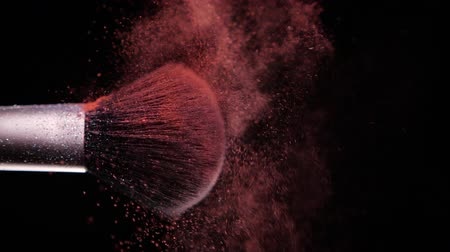 Make up brush with colored Red powder at black background Slow Motion