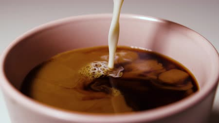 Slow motion of pouring milk into coffee drink.
