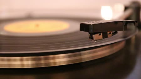 rpm : Video with running old gramophone turntable with disc. The needle is putting on rotating disc and taken down.