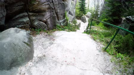 crevice : Walk down the stone stairs. A large sandstone rocks against a sky with a moving camera up. National Park Cesky Raj (Bohemian Paradise) in Czech Republic called Prachov Rocks (Prachov Rocks).