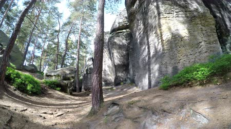 crevice : A large sandstone rocks in a forest against a sky with shinning sun. Camera turning left.