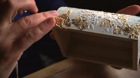 yaldız : Applying Gold Leaf. The Artist decorates the box with a sheet of gold. Restoration of the interior Stok Video
