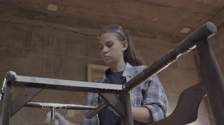 restaurálás : Girl carpenter, designer, decorator, works in a workshop on the restoration of old furniture
