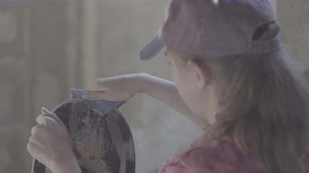 czapka : A girl in the workshop polished with sandpaper skateboard