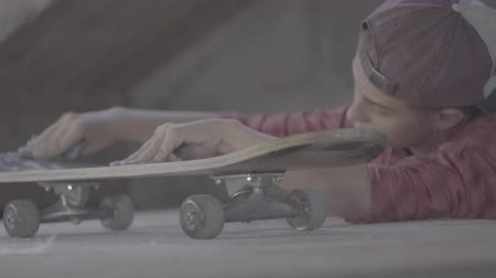 extreme close up : A girl in the workshop polished with sandpaper skateboard
