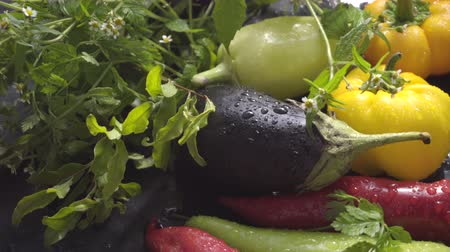 bakłażan : Vegetables, eggplants and peppers on a dark surface in drops of water in natural light