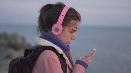 without face : Closeup portrait of a young woman standing on the beach with a smartphone at sunset Stock Footage