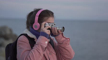 tomar : Girl in headphones takes a picture of the sea sunset on her vintage camera Stock Footage