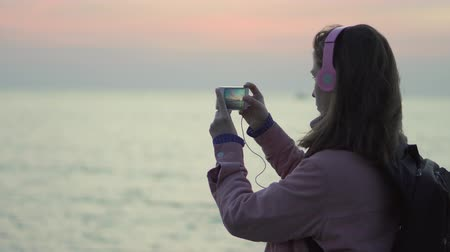 without face : A girl is taking pictures of the sea sunset using her smartphone Stock Footage