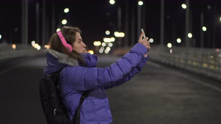 Girl talking on a video call using Mobile Phone During Walk on Streets of Night Town