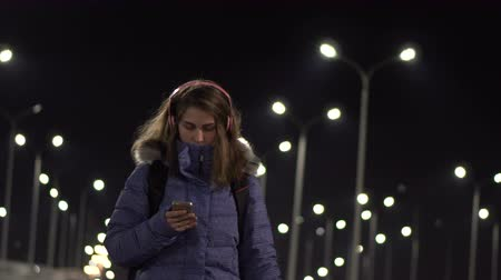 Attractive Woman using Mobile Phone During Walk on Streets of Night Town