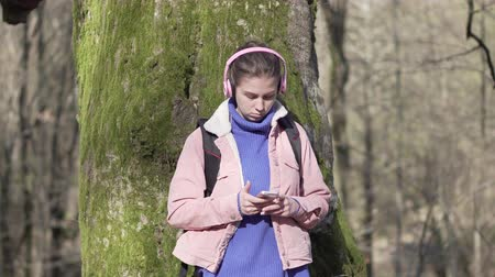 Traveler girl in the forest with mobile phone