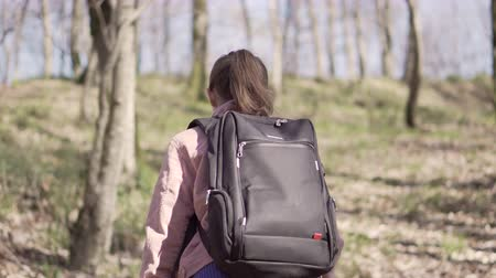 Girl traveler with a backpack travels in the forest Stock mozgókép
