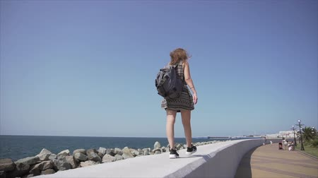 Girl with a backpack and headphones listens to music. Walks along the promenade.