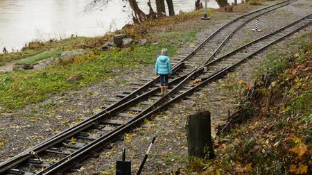 peril : Girl walking on train tracks. The girl at the crossroad. The child chooses the way.