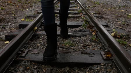 peril : Straight railway track in the rain. Woman steps on the straight railway track. Stock Footage