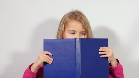 pára choque : The girl looks out from the book. Little girl spies of the big book. Blondy girl keeps an open big blue book.