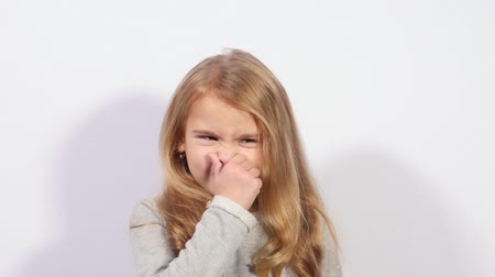 unpleasant smell : Girl holding her nose because of bad smell. A girl shows a gesture of bad smell. Funny girl shows dirty air. Stock Footage