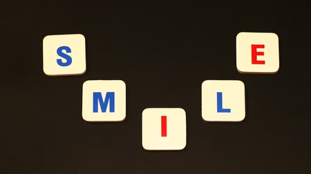 iyi olmak : Word smile layed out from letters in form of a smile. Smile on the black background. Stop motion
