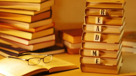 favori : A pile of books with the words READ ME appears on the table near the open book with glasses. Stop motion