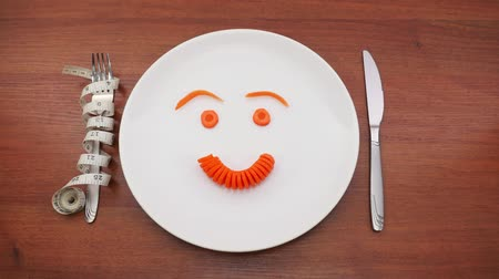 placas : Emoticons Carrot on a Plate. The sad and cheerful smiley of carrots on a white plate. Stop motion