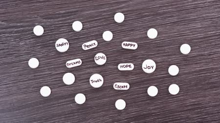 léčit : Words hope, love, joy, peace, dreams, escape, truth, sanity written on scattered drugs. Stop motion
