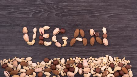 хорошее здоровье : Word vegan made of different nuts. Nuts fall and form a word vegan on the dark wooden background. Stop motion Стоковые видеозаписи
