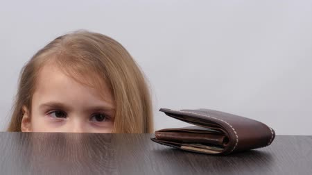 thieve : A girl looks out from under the table, slyly looks around and steals a purse from the table. Purse on the table. Girl looks aside and takes the wallet.
