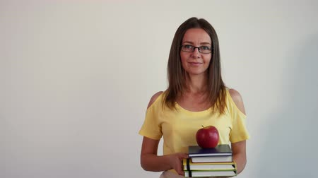 um : Young woman holding books and apple on the white background. The teacher adjusts her glasses. Stock Footage