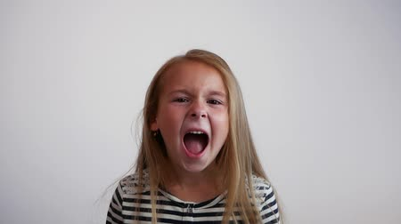 řvát : Pretty young girl shouting on white background. Slow motion Dostupné videozáznamy